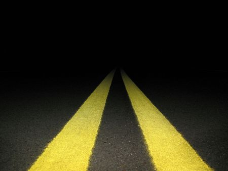 slow lane: Yellow center lines leading into the nights darkness,