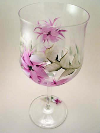 Floral wine glass with flower decorations wrapped around it.