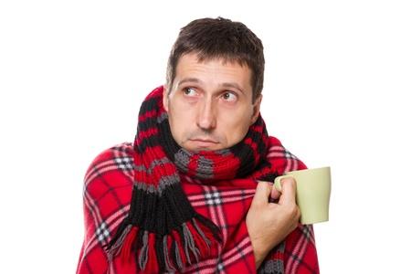 resfriado: el hombre resfriados envuelto en una manta caliente y una bufanda, sosteniendo una jarra Foto de archivo