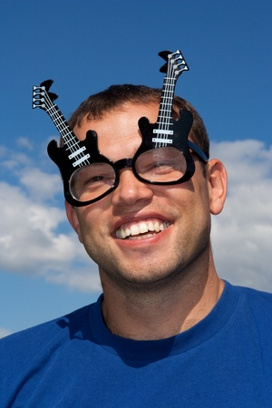 funny glasses: man in funny glasses on blue sky background