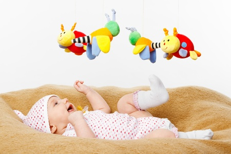 Happy smiling Baby lying on blanket and Playing with toys photo