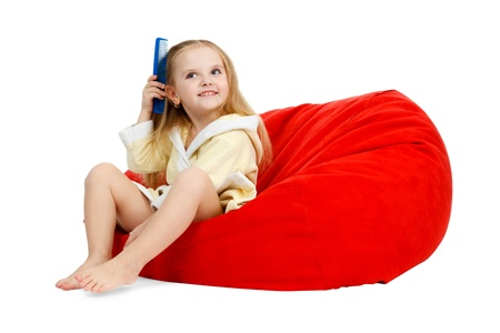 red bathrobe: little girl in a bathrobe combing your hair with a comb, sitting in a chair