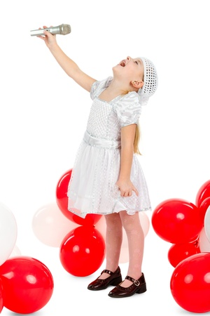 vocalist: little girl is singing with a microphone, standing next to balloons Stock Photo