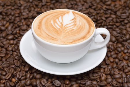 cappuccino: Coffee cup with coffee beans background Stock Photo