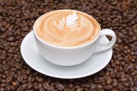 capuchino: Taza de caf� con granos de caf� de fondo