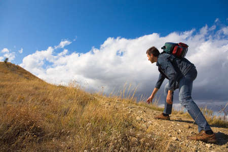 rock climbing man: man with backpack climbing a rock