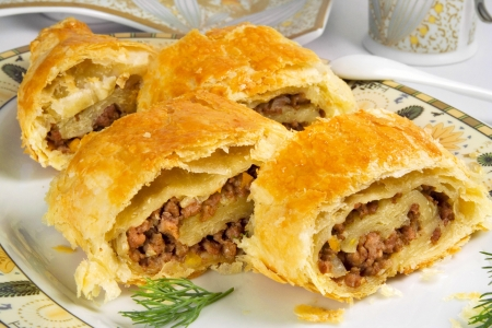 pastries: pie with ground beef filling, rolls of  puff pastry with meat on plate