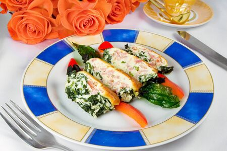 casserole with ham and spinach, sliced on plate, cup, bouquet of roses photo