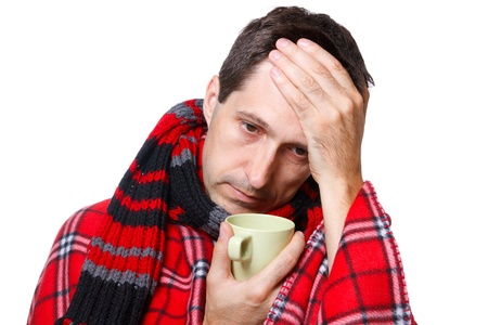 caucasian fever: cold man with flu wrapped in a warm blanket, holding a mug