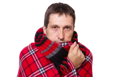 shivering: man wrapped in a warm blanket and scarf  shivering from the cold on white background