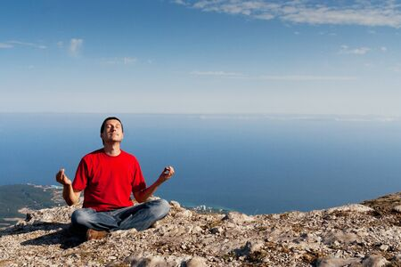 meditates: Happy man sits yoga pose meditates on the mountain Stock Photo