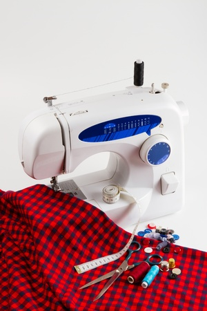 sewing machine with red cloth, buttons, spool of thread, scissors, measuring tape photo