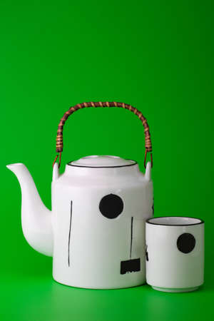 brewing: white porcelain teapot with wooden handle and cup on  bright green background