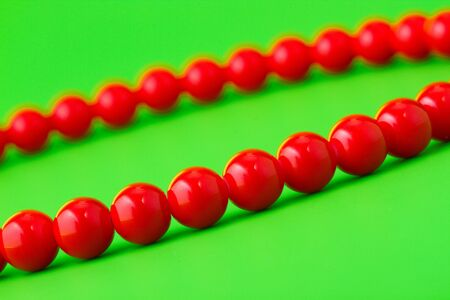 ladylike: red beads on green background