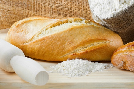 Freshly baked baguette and bread on wooden cutting board, sack of flour, rolling pin Stock Photo - 13324298