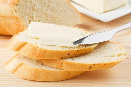 mantequilla: rebanada de baguette con mantequilla sobre tabla de madera