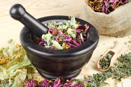 mortar and pestle and sack with healing herbs on wooden table Stock Photo - 13383410