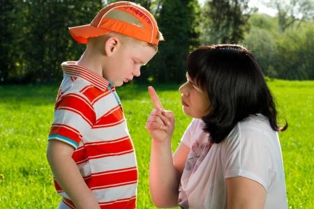 engedelmesség: Anya szidás fia hegyes ujját park Stock fotó