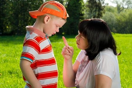 obedience: Madre regaña a su hijo con los dedos en punta en el parque Foto de archivo