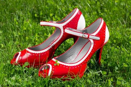 female red high heel summer shoe on green grass photo