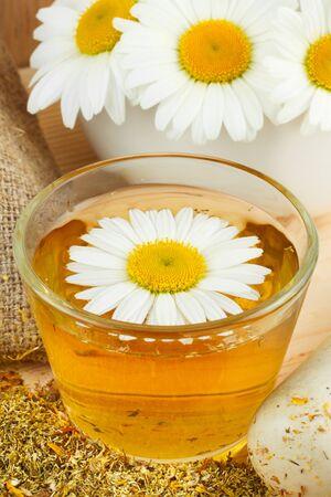 healthy chamomile tea, mortar with daisies photo