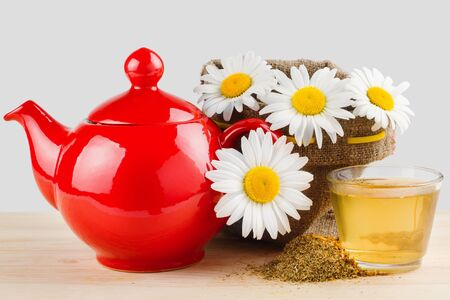 healthy chamomile tea, red teapot and sack with daisies photo