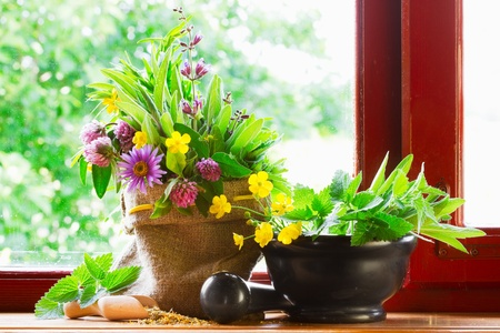 sack with bouquet of healing herbs and flowers, mortar and pestle on windowsill photo
