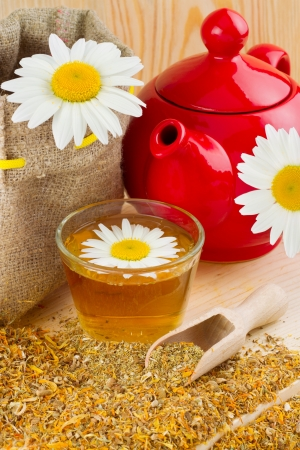 healthy chamomile tea, red teapot and sack with daisies Stock Photo - 14118630