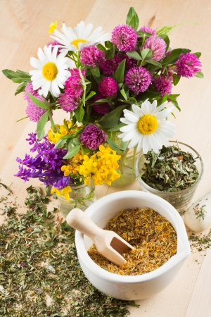 mortar with healing herbs, bouquet of daisy and clovers on wooden board, herbal medicine photo