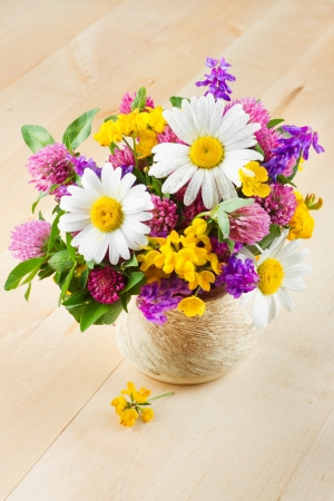 vase with bouquet of healing herbs and flowers on wooden table photo