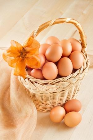 granja avicola: los huevos en una canasta sobre la mesa de madera