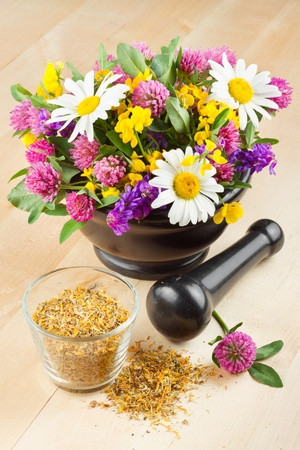 mortar with healing herbs and flowers, alternative medicine photo