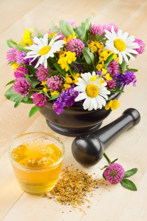 mortar with healing herbs and flowers, herbal tea on table, alternative medicine photo