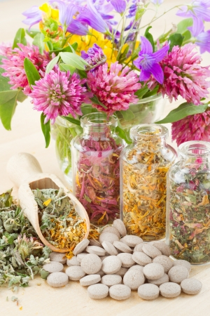 different healing herbs in glass bottles, flowers bouqet, tablets, herbal medicine photo