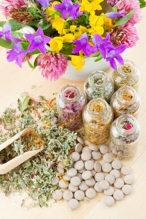 different healing herbs in glass bottles, flowers bouqet in mortar, tablets, herbal medicine, top view Stock Photo - 14118704