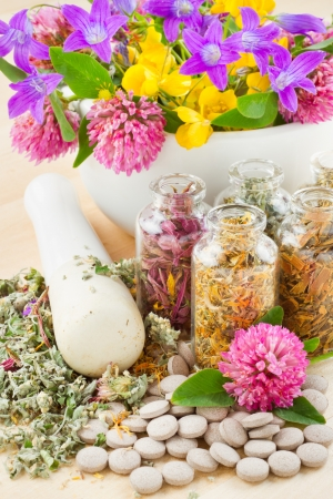 different healing herbs in glass bottles, flowers bouqet in mortar, tablets, herbal medicine Stock Photo - 14118700