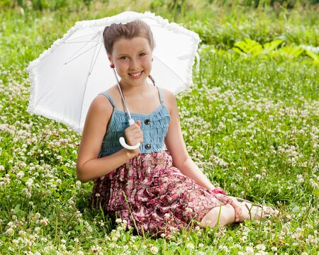 Smiling beautiful girl with umbrella sitting on a grass photo