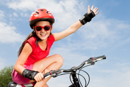 teenage girl on a bicycle with hand up photo