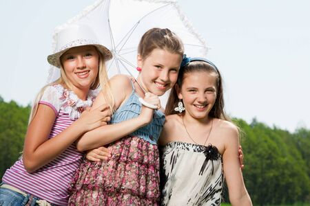 three happy young girl friends under umbrella photo