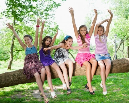 beautiful happy girls sitting on a tree trunk in park photo