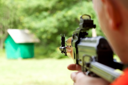 Man aiming at a target and shooting an automatic rifle  for strikeball  Focus on the rifle sights  photo