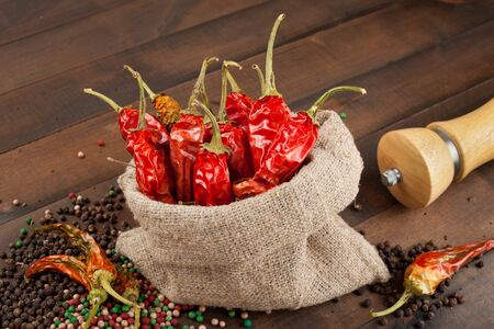 burlap sack: red chili peppers  in a canvas sack on wooden table Stock Photo