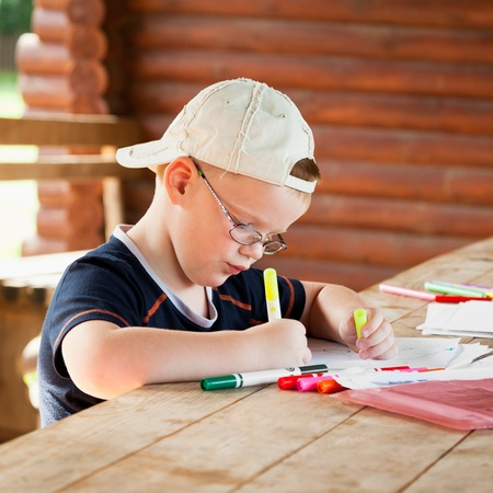 cute boy drawing in wooden gazebo outdoors Stock Photo - 16506440