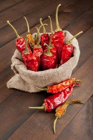 chiles picantes: rojo chiles en una bolsa de lona en la mesa de madera Foto de archivo