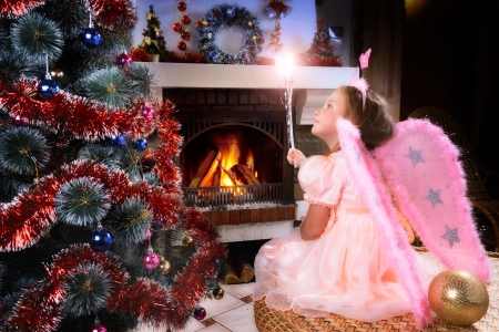 little fairy girl with magic wand near a Christmas tree, fireplace on background  photo