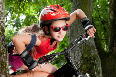 teenage girl on a bicycle, in park, outside