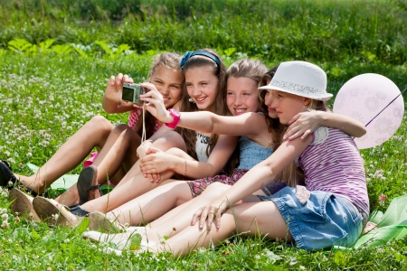 beautiful girls taking picture on grass in city park outdoors photo