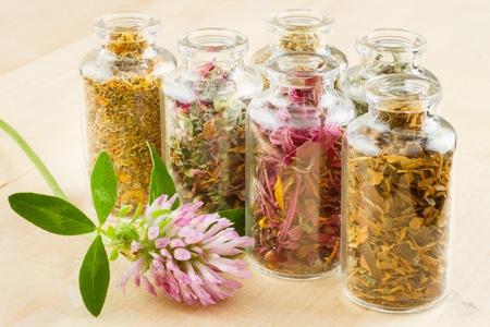 alternative medicine: healing herbs in glass bottles, herbal medicine