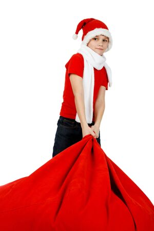 Boy in Santa Claus hat with red Christmas Gift Bag on white photo