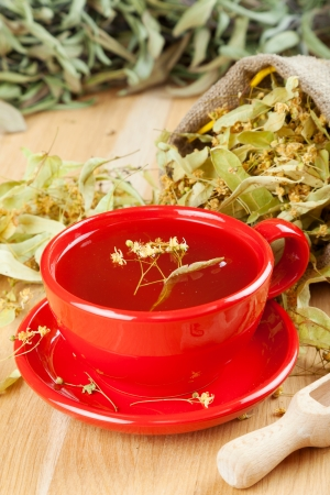 cup of linden tea and flowers in canvas bag on wooden table Stock Photo - 16508599